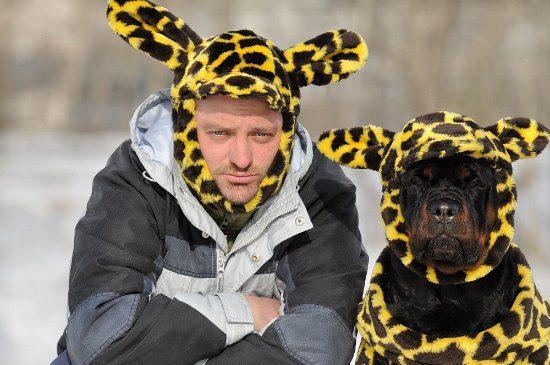 Ротвейлер со своим хозяином в смешных шапках.
